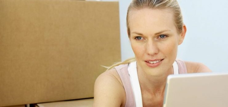 Woman using laptop and moving house