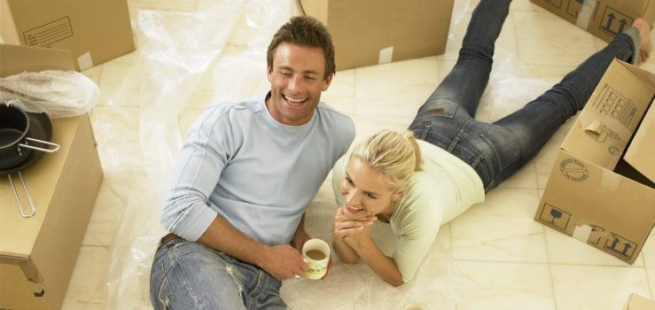 Couple with moving boxes waiting for long distance movers NJ