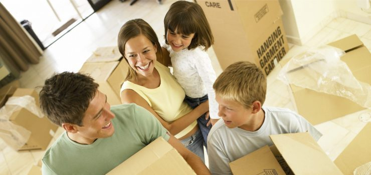 Family with moving boxes waiting for local movers NJ