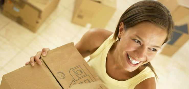 Woman with moving boxes and with good packing services NJ